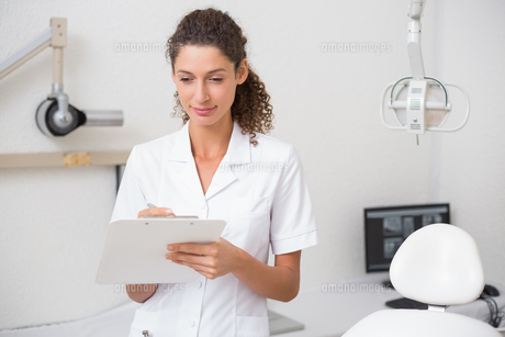 Dental assistant writing in clipboardの写真素材 [FYI00002780]