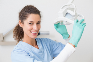 Dentist in blue scrubs smiling at camera beside lightの写真素材 [FYI00002781]