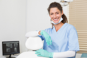 Dentist in blue scrubs smiling at cameraの写真素材 [FYI00002782]
