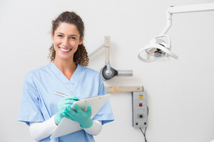 Dentist in blue scrubs writing on clipboardの写真素材 [FYI00002787]