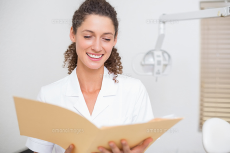 Dental assistant reading from fileの素材 [FYI00002789]