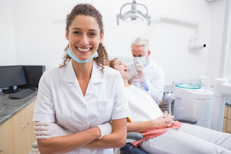 Dental assistant smiling at camera with dentist and patient behindの写真素材 [FYI00002791]