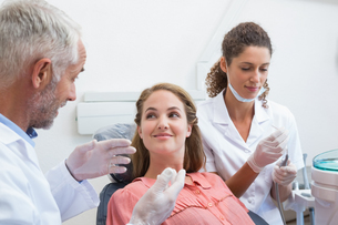 Dentist talking with patient while nurse prepares the toolsの写真素材 [FYI00002797]