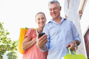 Happy senior couple looking at smartphone holding shopping bagsの写真素材 [FYI00002810]