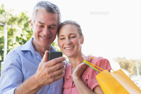 Happy senior couple looking at smartphone holding shopping bagsの写真素材 [FYI00002811]