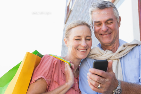 Happy senior couple looking at smartphone holding shopping bagsの写真素材 [FYI00002812]