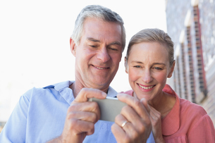 Happy senior couple looking at smartphoneの写真素材 [FYI00002816]