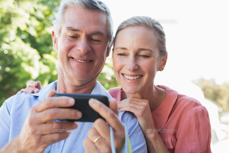 Happy senior couple looking at smartphoneの写真素材 [FYI00002817]