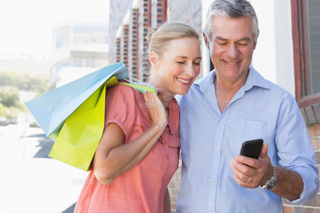 Happy senior couple looking at smartphone holding shopping bagsの写真素材 [FYI00002819]