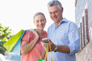 Happy senior couple looking at smartphone holding shopping bagsの写真素材 [FYI00002820]