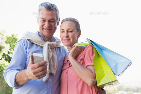 Happy senior couple looking at smartphone holding shopping bagsの写真素材 [FYI00002821]