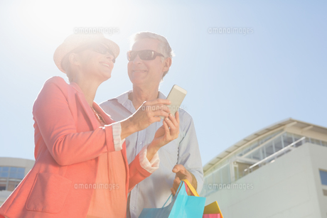 Happy senior couple looking at smartphone holding shopping bagsの写真素材 [FYI00002825]