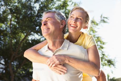 Happy senior man giving his partner a piggy backの写真素材 [FYI00002840]