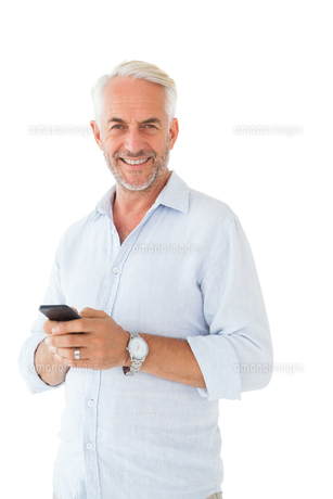 Smiling man sending a text messageの写真素材 [FYI00002846]