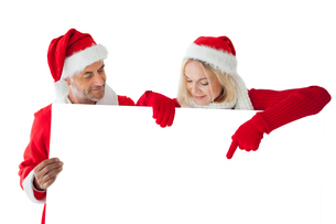 Festive couple pointing to large white cardの写真素材 [FYI00002847]
