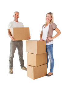 Happy couple smiling at camera with moving boxesの写真素材 [FYI00002848]