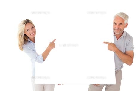 Happy couple holding and pointing to large posterの写真素材 [FYI00002862]