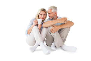 Happy couple sitting holding mugsの写真素材 [FYI00002863]