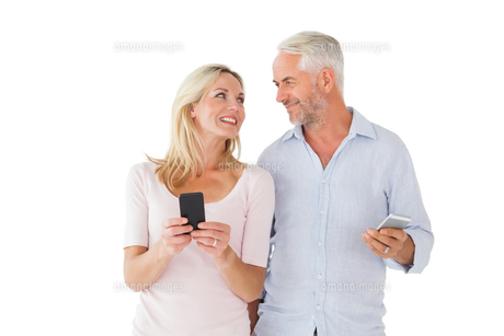 Happy couple texting on their smartphonesの写真素材 [FYI00002864]