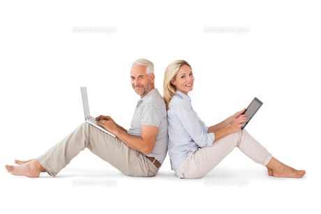 Happy couple sitting using laptop and tablet pcの写真素材 [FYI00002865]