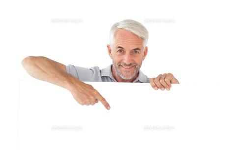 Smiling man showing large posterの写真素材 [FYI00002869]