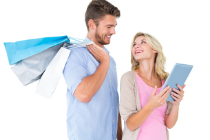 Attractive young couple holding shopping bags looking at tablet pcの写真素材 [FYI00002877]