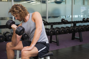 Young man exercising with dumbbell in gymの写真素材 [FYI00002893]