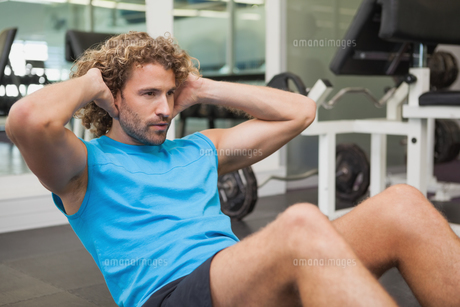 Handsome man doing abdominal crunches in gymの写真素材 [FYI00002894]