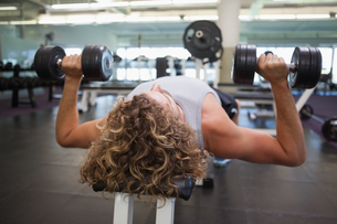 Young man exercising with dumbbells in gymの写真素材 [FYI00002895]