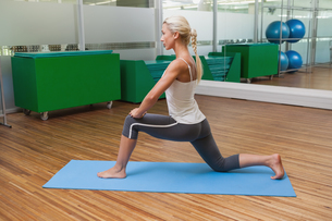 Fit woman doing stretching exercise in gymの写真素材 [FYI00002897]