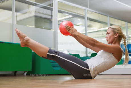 Side view of woman in boat pose at fitness studioの写真素材 [FYI00002899]