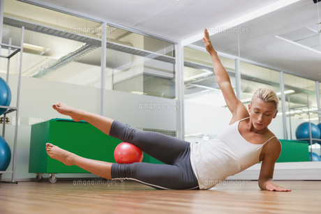 Full length of woman doing fitness exercise in gymの写真素材 [FYI00002900]