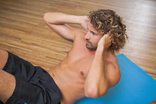 Shirtless young man doing push ups in gymの写真素材 [FYI00002901]