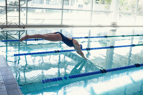 Side view of swimmer diving into pool at leisure centerの写真素材 [FYI00002902]