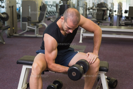 Young man exercising with dumbbell in gymの写真素材 [FYI00002903]