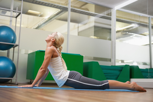 Side view of woman stretching her back in fitness studioの写真素材 [FYI00002904]