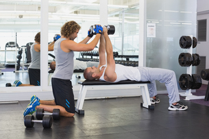Male trainer assisting young man with dumbbells in gymの写真素材 [FYI00002912]