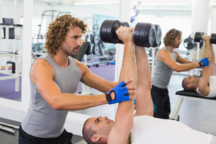 Male trainer assisting man with dumbbells in gymの写真素材 [FYI00002914]