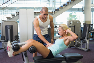 Male trainer assisting woman with abdominal crunches at gymの写真素材 [FYI00002915]