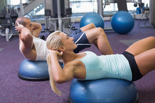 Fit couple doing abdominal crunches at gymの写真素材 [FYI00002916]