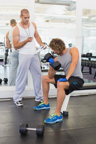 Male trainer assisting man with dumbbell in gymの写真素材 [FYI00002917]