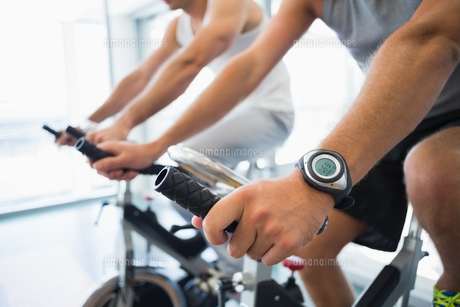 Mid section of men working on exercise bikes at gymの写真素材 [FYI00002918]