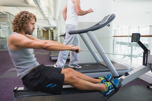 Fit young man on fitness machine at gymの写真素材 [FYI00002921]
