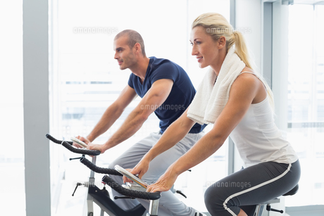 Determined couple working on exercise bikes at gymの写真素材 [FYI00002923]