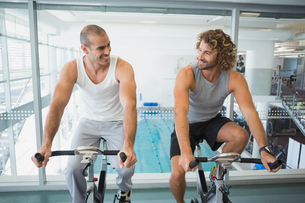Fit men working on exercise bikes at gymの写真素材 [FYI00002924]