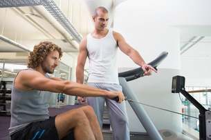 Male trainer assisting man on fitness machine at gymの写真素材 [FYI00002930]