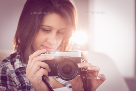Pretty brunette looking at retro camera on couchの写真素材 [FYI00002947]