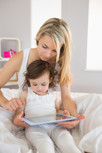 Mother and daughter using digital tablet on bedの写真素材 [FYI00002952]