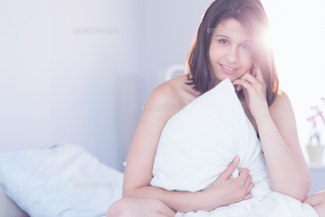 Beautiful brunette hugging her pillowの写真素材 [FYI00002954]