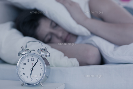 Beautiful brunette blocking the noise from alarm clock in her bedの写真素材 [FYI00002955]